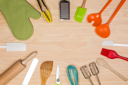 colorful kitchen utensils on wooden background Stock Photo