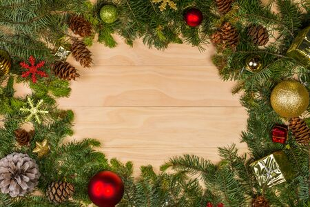 green frame: pine cones and branches with christmas decoration on wooden background Stock Photo