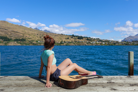 young woman sitting on pier and enjoy the view of the lake and mountain