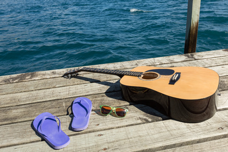 Acoustic guitar and flip flops on a dock by the lake Stok Fotoğraf - 49944599