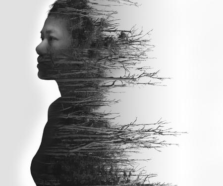 retrato de la doble exposición de la mujer joven y bosque muerto en blanco y negro Foto de archivo