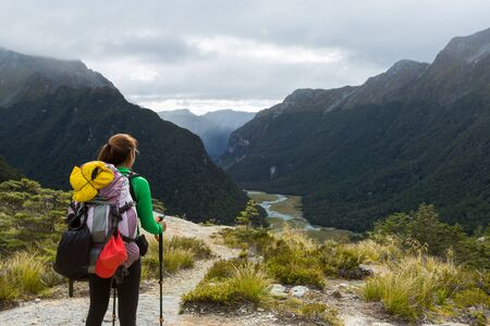 woman hiker with backpack looking at the view of Routeburn Flat from Routeburn Falls, New Zealand