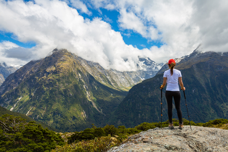 Woman hiker standing on a cliff and enjoys the view of Key Summit with Ailsa Mountain at the background. Routeburn Track, New Zealand