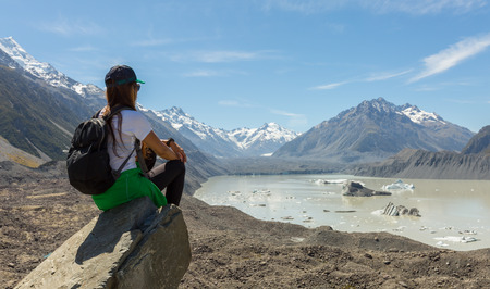 aoraki mount cook national park: woman hiker with backpack sit at the edge of the cliff and look at Tasman Glacier Lake. Mt Cook National Park, New Zealand