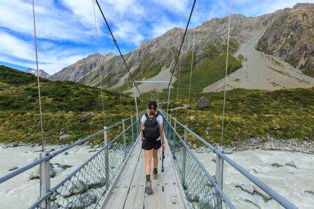 aoraki mount cook national park: Woman hiker walking on the bridge over Hooker river
