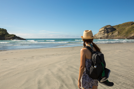 nelson: Young adult woman walking on Wharariki Beach in New Zealand