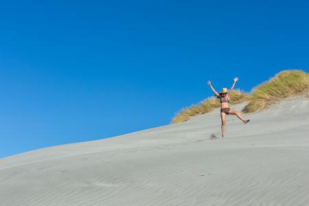 aotearoa: woman traveler jumping on the sand dune at Wharariki Beach in New Zealand