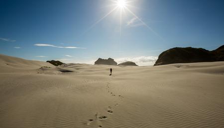 aotearoa: Woman traveler walking on sand dune at Wharariki Beach in New Zealand