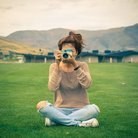young adult woman taking a photo with a retro camera, filtered in vintage