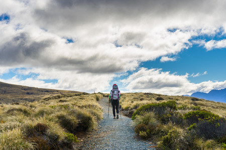anau: Woman hiker walking on Kepler Track, one of the New Zealand Great Walks Stock Photo