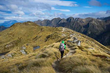 kepler: Woman hiker walking on an alpine section of the Kepler Track, one of the New Zealand Great Walks