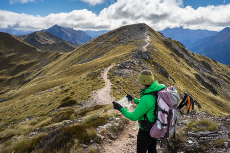kepler: Woman hiker looing at the map of Kepler Track, one of the New Zealand Great Walks