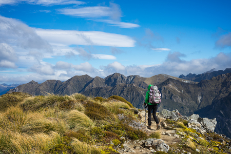 anau: Woman hiker walking on an alpine section of the Kepler Track, one of the New Zealand Great Walks