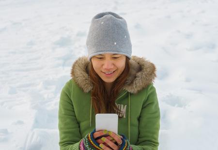 coronet: Happy woman using mobile phone at ski field at Coronet peak