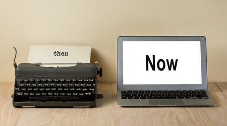 then: vintage typewriter and computer laptop with words now and then Stock Photo