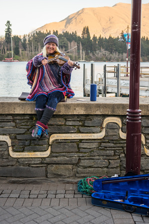 busker: Queenstown, New Zealand - June 30, 2016: A lady busker plays violin at the lake front at Earnslaw Park in Queenstown.