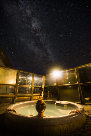 Back view of a young woman enjoying hot tub under the stars and milky way in New Zealand Stok Fotoğraf - 68447528