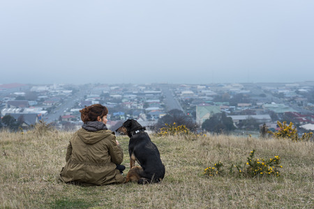 oamaru: Young adult woman sitting with her dog on the hill in Oamaru, New Zealand