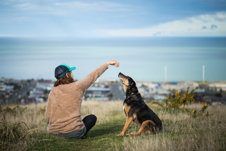 Adult woman sitting her dog on the hill