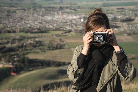 Woman tourist taking photograph with retro camera
