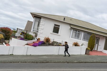 oamaru: Oamaru, New Zealand - September 20, 2016: Woman tourist, Kwankhao Pai-Roah walks on Tyne street, one of the steepest street in Oamaru. Editorial