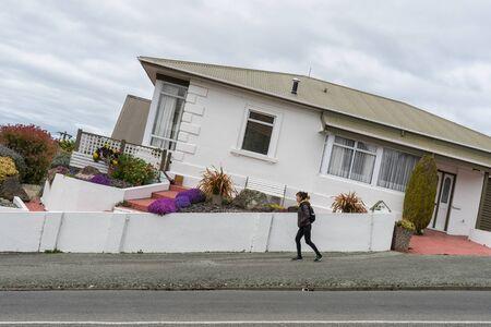 Oamaru, New Zealand - September 20, 2016: Woman tourist, Kwankhao Pai-Roah walks on Tyne street, one of the steepest street in Oamaru. Stok Fotoğraf - 68683357