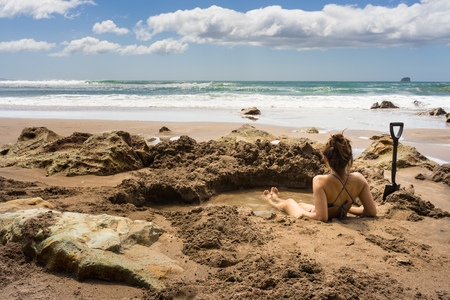 Frau in heißem Wasser Thermalbecken sitzen in Hot Water Strand in Mercury Bay, Coromandel, Neuseeland Standard-Bild - 69092123