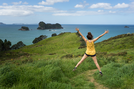 Young woman jumping on green field at Coromandel Peninsula
