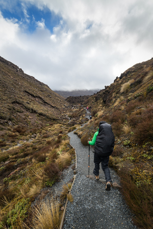 Woman hiker with backpack tramping on Tongariro national park in New Zealand Stok Fotoğraf - 70251885