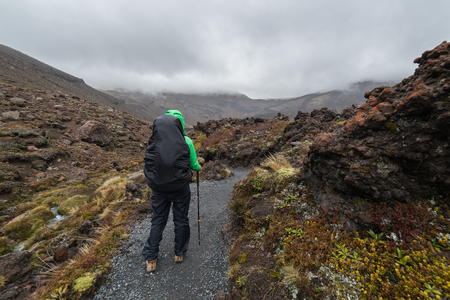 Woman hiker with backpack tramping on Tongariro national park in New Zealand Stok Fotoğraf