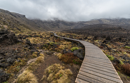 Wooden boardwalk with Volcanic rocks formation alongside in Tongariro national park, New Zealand
