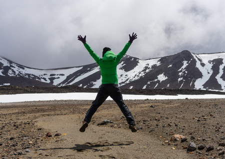 Happy woman hiker jumping in Tongariro national park in New Zealand Standard-Bild