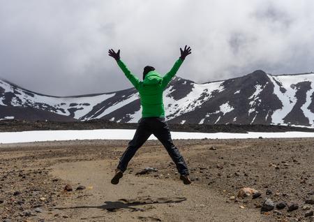 Glücklicher Frauenwanderer, der in Nationalpark Tongariro in Neuseeland springt Standard-Bild - 70259693
