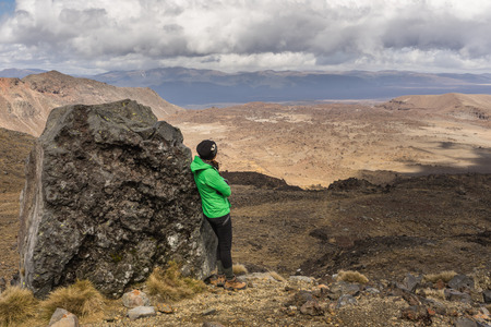 Woman hiker leaning against the volcanic rock and enjoy the view of Tongariro national park in New Zealand