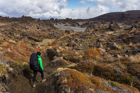 Woman hiker walking on dessert area full of volcanic rocks formations in Tongariro national park, New Zealand