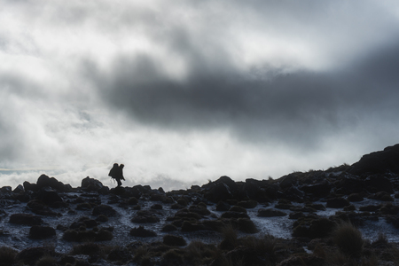 Silhouette image of woman hiker with backpack walking on the hill