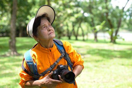 Grandmother with camera.Elderly activities. Archivio Fotografico