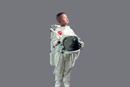 Kleiner Junge im Raumanzug. Kind im Raumanzug. Die Traumjobs der Kinder. Netter kleiner Junge im Raumanzug, der Helm hält und in die Ferne schaut