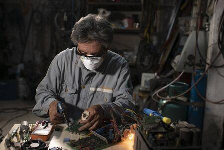 Senior Man in gray Work Coat is Using Plier to Assemble Circuit board. Archivio Fotografico
