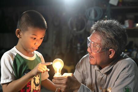 Cute boy learning with his grandfather.It is interesting to learn. Banco de Imagens