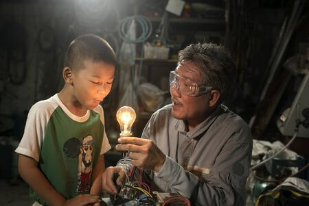 Cute boy learning with his grandfather.It is interesting to learn. Archivio Fotografico