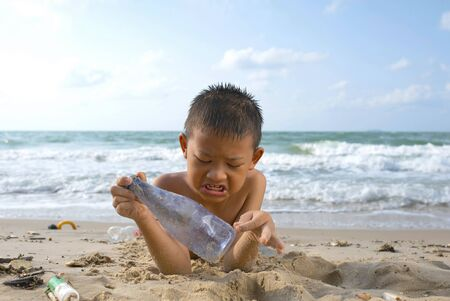 Child lay down on the beach and picks up dirty bottles at the beach. A boy picks up dirty plastic bottles at the beach.