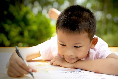 Elementary age boy writing in book while lying down on floor.A boy lie down writing in a book. Archivio Fotografico