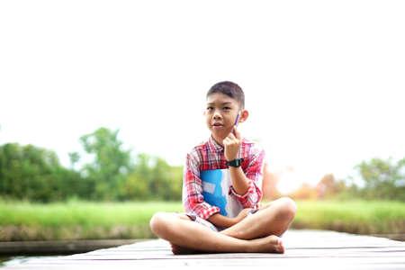 Outdoor portrait of cute boy sitting on wooden bridge at park.