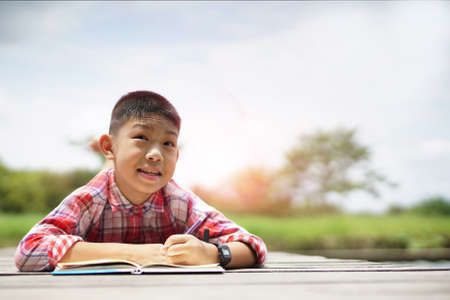 Adorable boy lying down on the bridge floor writing book at park.