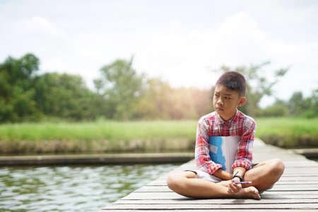 Portrait of sad child boy  thinking on the bridge in summer day.