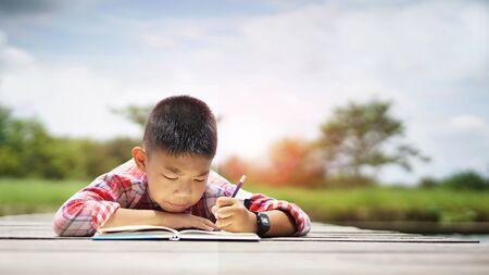 Little boy lying on bridge floor and writing book at park. Little boy lying on the floor with writing book at park.