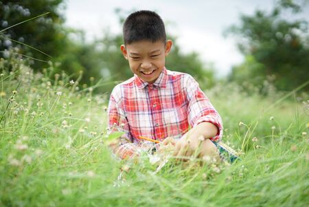 Portrait of smiling child boy with writing book on the grass in summer day.