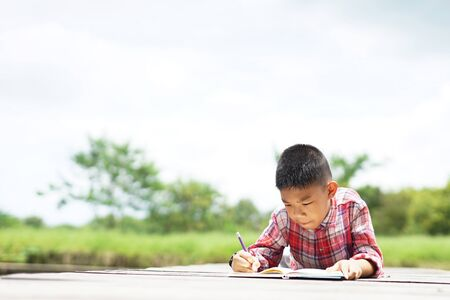 Adorable boy lying down on the floor at park.Little boy lying on floor and writing book.
