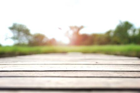 Wood plank bridge on green grass field. Gray wooden bridge near green grass field.